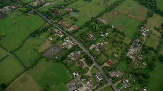 AX114_332 - 6K stock footage aerial video tilt to bird's eye view of farm fields and rural homes, Windsor, England