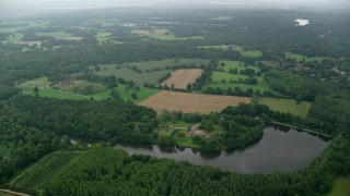 AX114_340 - 6K stock footage aerial video of Great Pond and farm fields surrounded in trees, Ascot, England