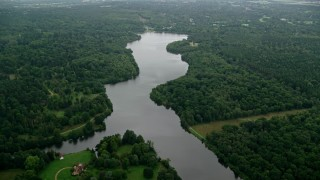 AX114_344 - 6K stock footage aerial video fly over Virginia Water Lake and trees, England