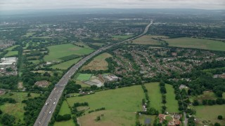 AX114_352 - 6K stock footage aerial video of light traffic on M25 Freeway toward residential homes, Chertsey, England