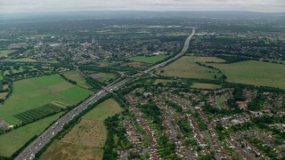 AX114_353 - 6K stock footage aerial video approach M25 Freeway from neighborhoods, Chertsey, England