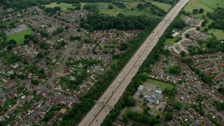 AX114_355 - 6K stock footage aerial video of M25 Freeway by residential neighborhoods, Addlestone, England