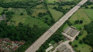 AX114_356 - 6K stock footage aerial video of flying over M25 Freeway past farm fields, Addlestone, England