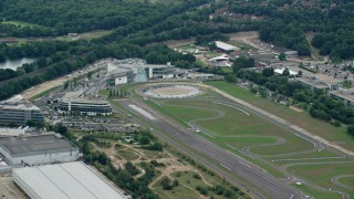AX114_358 - 6K stock footage aerial video of orbiting office buildings and a race track, Weybridge, England