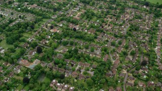 AX114_369 - 6K stock footage aerial video fly over tree-lined neighborhoods in Leatherhead, England