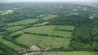 AX114_370 - 6K stock footage aerial video tilt from homes to reveal farm fields, Leatherhead, England