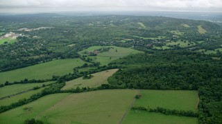 AX114_371 - 6K stock footage aerial video fly over farm fields by forests, Leatherhead, England