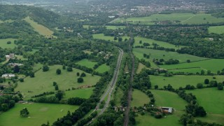 AX114_372 - 6K stock footage aerial video of orbiting a country road and farm fields, Leatherhead, England