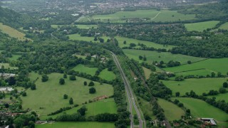 AX114_373 - 6K stock footage aerial video of a country road and farming fields with trees, Leatherhead, England