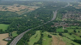 AX114_380 - 6K stock footage aerial video of orbiting freeway through trees, Redhill, England