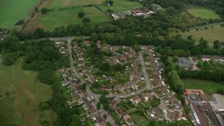 AX115_001 - 6K stock footage aerial video fly over homes and farmland, Redhill, England