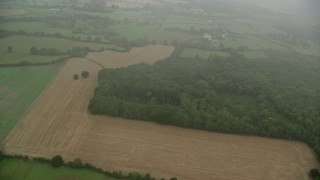 AX115_002 - 6K stock footage aerial video tilt from farm fields and forests to reveal fog, Redhill, England