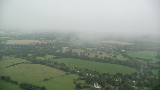 AX115_003 - 6K stock footage aerial video of flying through low clouds by farms and trees, Redhill, England