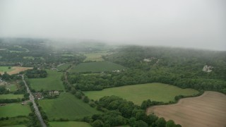 AX115_005 - 6K stock footage aerial video approach homes by train tracks and farmland in Betchworth, England