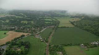 AX115_006 - 6K stock footage aerial video follow train tracks near homes and farm fields, Betchworth, England