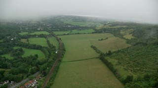 AX115_007 - 6K stock footage aerial video pan from train tracks while flying over farmland in Betchworth, England