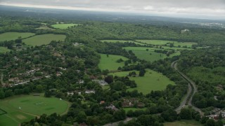 AX115_008 - 6K stock footage aerial video of flying over freeway near village, farm fields, and forests, Dorking, England