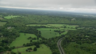 AX115_009 - 6K stock footage aerial video of flying by forest and farming fields, Dorking, England