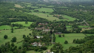AX115_010 - 6K stock footage aerial video approach a small village with homes by farm fields, Mickleham, England