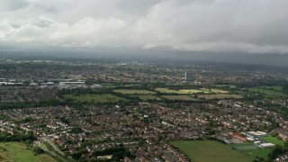 AX115_013 - 6K stock footage aerial video of flying over residential neighborhoods toward warehouses, Chessington, England