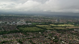 AX115_014 - 6K stock footage aerial video fly over homes while approaching warehouses, Chessington, England