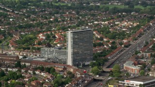 AX115_015 - 6K stock footage aerial video of orbiting an office building beside residential area, Tolworth, England
