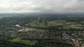 AX115_018 - 6K stock footage aerial video fly over residential neighborhoods toward Hampton Court Palace and the park, England