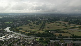 AX115_019 - 6K stock footage aerial video approach Hampton Court Palace and Park in Molesey, England