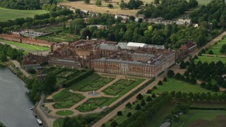AX115_031 - 6K stock footage aerial video of circling Hampton Court Palace by River Thames in Molesey, England