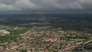 AX115_043 - 6K stock footage aerial video of a rainbow over residential neighborhood, Morden, England