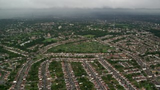 AX115_049 - 6K stock footage aerial video fly over suburban homes with rain in the distance, London, England