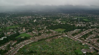 AX115_050 - 6K stock footage aerial video fly over residential neighborhoods approaching rain in the distance, London, England