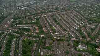 AX115_054 - 6K stock footage aerial video of flying over residential neighborhoods in the rain, London, England