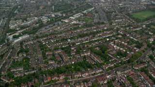 AX115_055 - 6K stock footage aerial video of residential neighborhoods in the rain, London, England