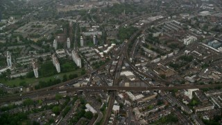 AX115_056 - 6K stock footage aerial video fly over residential area with train tracks in the rain, London, England
