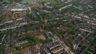 AX115_057 - 6K stock footage aerial video tilt to St John the Divine church by apartment buildings in the rain, London, England