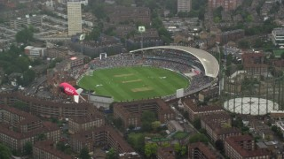 AX115_059 - 6K stock footage aerial video of orbiting The Oval cricket stadium in the rain, London, England
