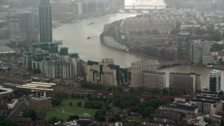 AX115_060 - 6K stock footage aerial video of orbiting MI6 Building in the rain, London, England