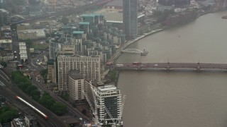 AX115_062 - 6K stock footage aerial video of orbiting MI6 Building and Vauxhall Bridge in the rain, London, England