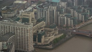 AX115_063 - 6K stock footage aerial video of orbiting MI6 Building in the rain, London, England