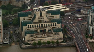 AX115_066 - 6K stock footage aerial video of orbiting the MI6 Building by busy streets in the rain, London, England