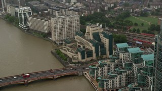 AX115_069 - 6K stock footage aerial video of orbiting the MI6 Building revealing skyscraper in the rain, London, England
