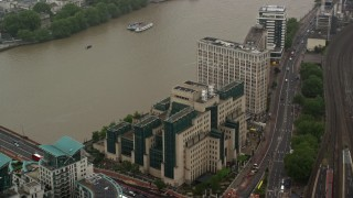 AX115_071 - 6K stock footage aerial video of orbiting MI6 Building and River Thames in the rain, London, England