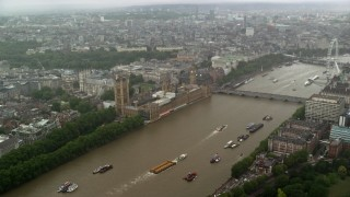 AX115_072 - 6K stock footage aerial video approach Big Ben and Parliament from River Thames in the rain, London, England