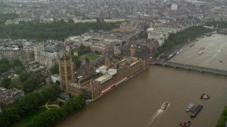 AX115_073 - 6K stock footage aerial video approach Big Ben and Parliament from the river in the rain, London, England