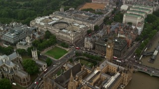 AX115_074 - 6K stock footage aerial video fly over Big Ben and Parliament toward Treasury and Foreign Office in the rain, London, England