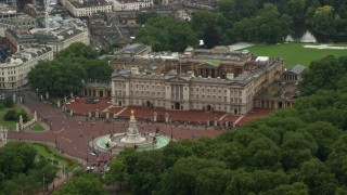 AX115_076 - 6K stock footage aerial video of orbiting Buckingham Palace and Victoria Memorial while raining, London, England