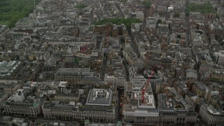 AX115_077 - 6K stock footage aerial video tilt from office buildings in the rain to wider view of the city, London, England