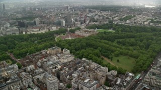 AX115_078 - 6K stock footage aerial video approach Buckingham Palace from office buildings in the rain, London, England