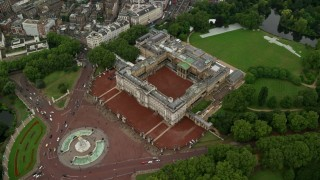 AX115_080 - 6K stock footage aerial video tilt to bird's eye of Buckingham Palace in the rain, London, England